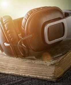 Image of Earphones resting on top of open book.