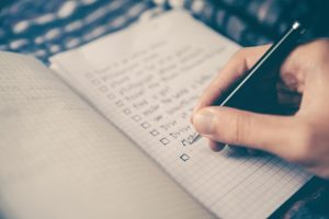 person writing checklist unsplash photo by Glenn Carstens-Peters