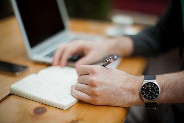 man writing prolific writers life photo by Alejandro Escamilla